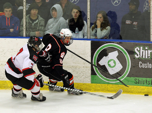 Salem: Beverly sophomore defenseman Nick Albano tries to shield Marblehead freshman Matt Koopman from the puck as it skids down the boards. David Le/Salem News