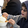"Danvers: Michael Kelley, 11, of Lynn, scoops some whipped cream off the top of his waffle ice cream sundae at Cherry Farm Creamery in Danvers, during their annual ""Ice Cream for Breakfast"" fundraiser on Saturday morning. David Le/Salem News"
