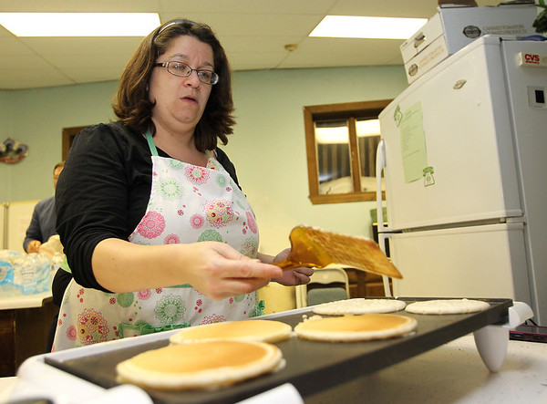 Danvers: Sarah Patrick, of Lynn flips over some pancakes during a busy hour at the All Episcopal Church's first Shrove Tuesday Pancake and Sausage Supper. David Le/Salem News