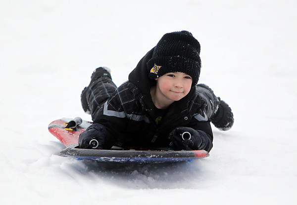 Salem: Josh Downy, 6, of Beverly slides headfirst down a hill at Kernwood Country Club on Tuesday afternoon. David Le/Salem News
