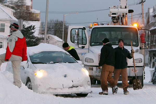 Swampscott: A few National Grid workers help dig out a car which got stuck in deep snow along Humphrey St. in Swampscott on Saturday afternoon. David Le/Salem News