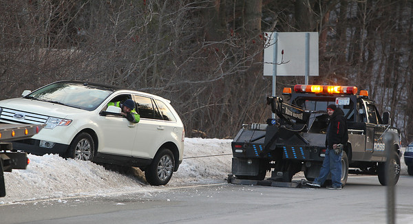 Wenham: Tow truck workers pull a car that got lodged in a snowbank on the Rt. 128 North exit 17 off-ramp on Wednesday afternoon. David Le/Salem News