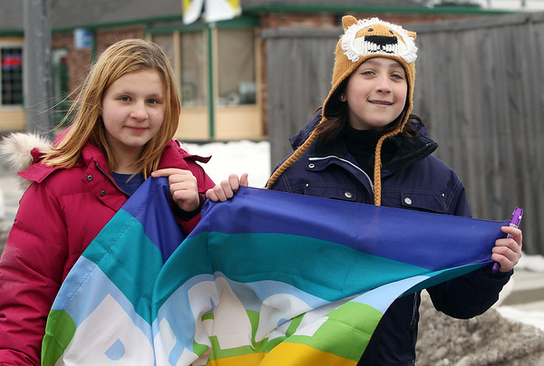 Salem: Ten-year-old Lily Gindes, left, and eleven-year-old Cooper Sherf, both of Marblehead, hold a peace flag as they march down Bridge St. in Salem as part of the Salem Peace Committee's annual Walk for Peace on Tuesday afternoon. David Le/Salem News