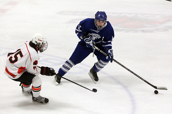 Woburn: Danvers junior Ryan Cassidy plays the puck up the boards while being pursued by Beverly sophomore Jesse McLaughlin on Friday evening. David Le/Salem News