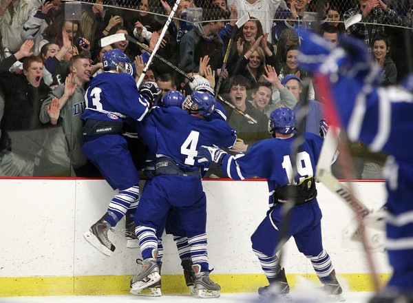 Woburn: The Danvers Falcons jump in exuberance against the boards after completing a 4-3 upset over top ranked Beverly on Friday evening. David Le/Salem News