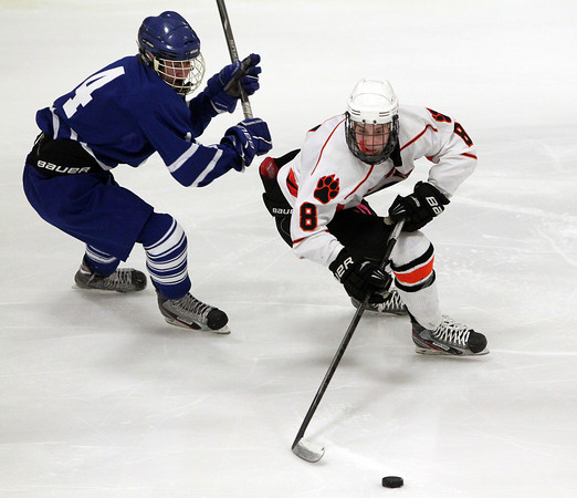 Woburn: Beverly sophomore defenseman Nick Albano controls the puck while being pursued by Danvers junior forward Matt Flynn on Friday evening. David Le/Salem News
