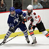 Woburn: Danvers junior captain Kevin Hodgkins plays the puck out of the zone while being pursued closely by Beverly sophomore forward Ted Leathersich on Friday evening. David Le/Salem News