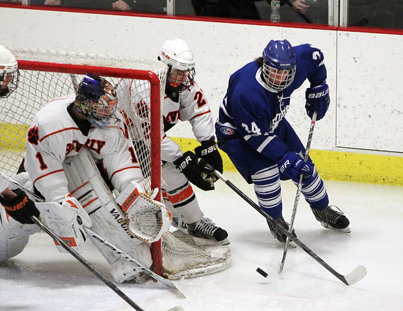 Woburn: Danvers senior winger Adam Merry tries to get a shot off on Beverly sophomore goalie Tim Birarelli while being pursued by junior Graham Doherty, center, on Friday evening. David Le/Salem News