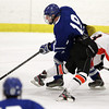 Woburn: Danvers senior captain Rob Buchanan steps around the hip check from Beverly sophomore defenseman Nick Albano and closes in on goal on Friday evening. David Le/Salem News