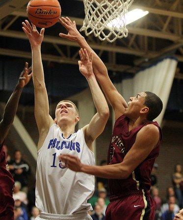 Byfield: Danvers senior captain Nick Bates gets a layup off just before a block attempt from Whittier Tech senior Justin Reyes, right, during the fourth quarter of play on Tuesday evening. David Le/Salem News