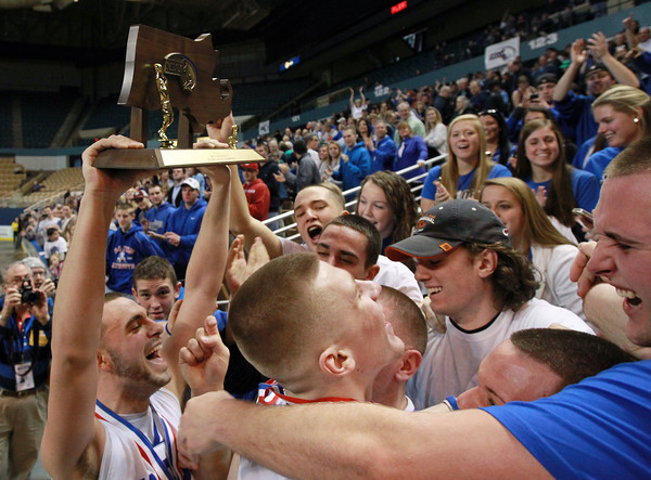 Worcester: Danvers senior captain Nick McKenna, left, holds up the D3 State Championship trophy high above his head for all the Danvers fans gathered at the DCU Center in Worcester to see. McKenna and the Falcons won their second State Title in as many years with a 66-50 win over Smith Academy. David Le/Salem News