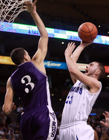 Boston: Danvers senior captain Nick McKenna releases a floater over the block attempt from Martha's Vineyard senior Izak Browne, left, during the fourth quarter of play.  David Le/Salem News