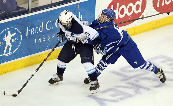 Lowell: Danvers senior Joe Strangie throws a check into the body of Wilmington senior Cam Owens, left, as he controls the puck behind the Falcons net. Strangie and the Falcons fell to the Wildcats 7-2 in the D2 North Final on Monday evening. David Le/Salem News