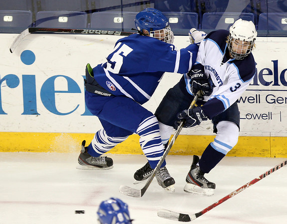 Lowell: Danvers sophomore defenseman Stephen Ganley, left, makes a hard check on Wilmington senior Jake Rogers, separating him from the puck during the second period of play. David Le/Salem News