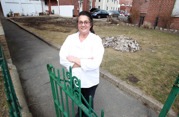 Salem: Karen Andrew, Kitchen Manager at the Lifebridge Center in Salem, stands at the gateway for the new vegetable garden in a yard that once had a religious grotto for St. Mary's Italian Church. David Le/Salem News
