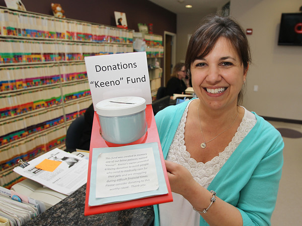 """Peabody: Donna DiMare, Office Manager of the Northeast Veterinary Hospital on Lowell St. in Peabody holds up a jar for donations to the """"Keeno"""" Fund, a donation jar set up to help families in need with pet care. David Le/Salem News"""