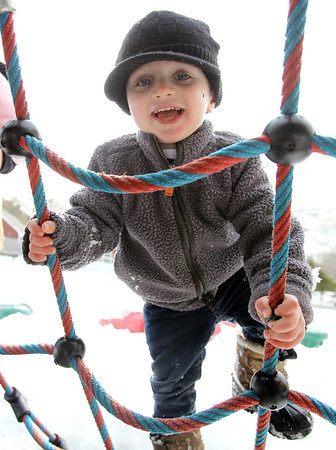 Beverly: Asher Stern, 2 1/2, of Beverly smiles while climbing up a rope ladder at Kimball Haskell Park in Beverly on a warm Monday afternoon. David Le/Salem News