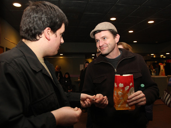 """Salem: Sean McCrea, right, of Salem, hands his ticket to Cinema Salem employee Nick Henry on his way into see """"West of Memphis,"""" a new film about the West Memphis Three including current Salem resident Damien Echols, at the Salem Film Fest on Friday evening. David Le/Salem News"""