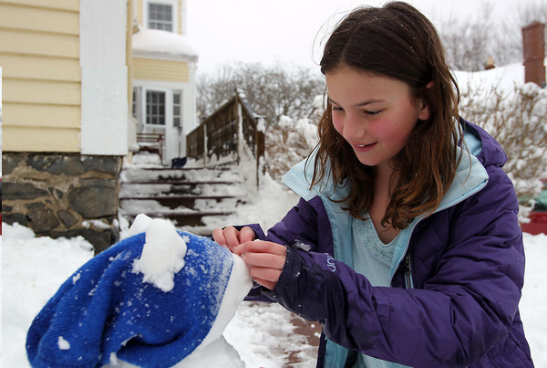 """Marblehead: Lauren Podgur, 9, of Marblehead, enjoys her snow day from school by carefully placing a nose on her """"snow dog"""" on Friday afternoon. David Le/Salem News"""