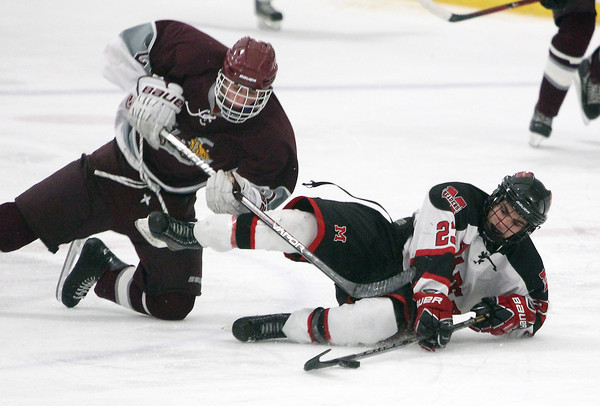 Stoneham: Marblehead senior forward Aaron DeAngelo, right, plays the puck while sliding across the ice while being pressured by Rockport junior Dane Tolstrup, left, on Saturday evening. David Le/Salem News