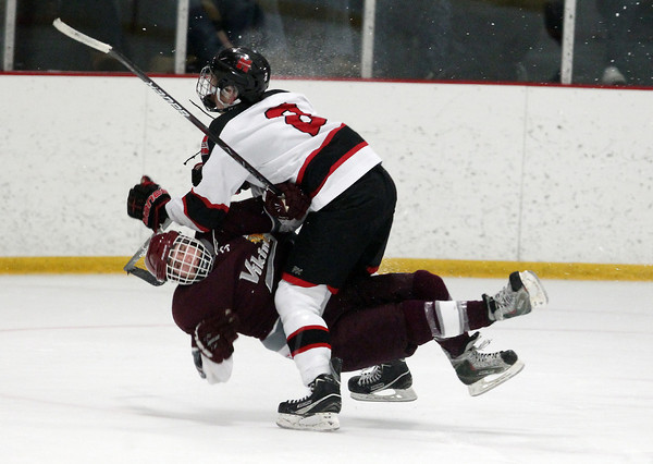 Stoneham: Marblehead senior forward Ian Maag delivers a hit that lifts Rockport senior Alex Amoroso off his feet and separates him from the puck. David Le/Salem News