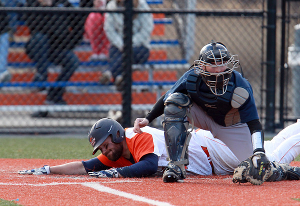 Salem: Salem State junior Mike Lamothe, left, safely slides headfirst into home plate while the Suffolk University catcher awaits the throw. David Le/Salem News