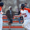 Salem: Salem State University junior Mike Lamothe, right, gets a high five from sophomore teammate Ryan Beliveau, left, after Lamothe slid safely home for a Vikings' run. David Le/Salem News
