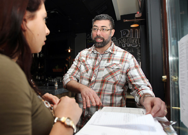 Dave Gillis, owner of Salt Kitchen and Rum Bar in Ipswich, talks with hostess Breanna Smith prior to opening last week. David Le/Salem News
