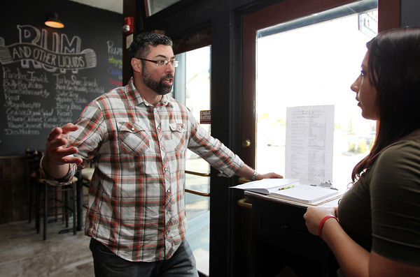 Dave Gillis, owner of Salt Kitchen and Rum Bar in Ipswich, talks with hostess Breanna Smith, right, prior to opening. David Le/Salem News