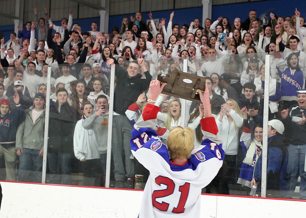 Stoneham: Swampscott junior Nunzio Morretti holds the D3 North Championship trophy high above his head for the whole Big Blue fan section to see after Swampscott defeated Bedford 3-2 on Saturday afternoon. David Le/Salem News