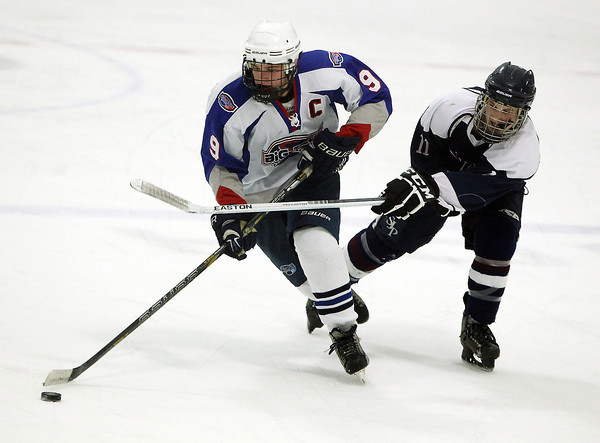 Stoneham: Swampscott senior captain Trevor Massey carries the puck up-ice while being hassled by St. Joseph's Prep sophomore Alex Watson, right, on Saturday afternoon. The Big Blue handily beat St. Joseph's 10-1, earning them their first tournament win in 44 years. David Le/Salem News