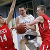 Hamilton: Hamilton-Wenham junior Henry Eagar, center, gets fouled as he splits Masco's Alberto Arenaza, left, and Zach Turcotte, right, on his way to the basket on Tuesday evening. David Le/Salem News