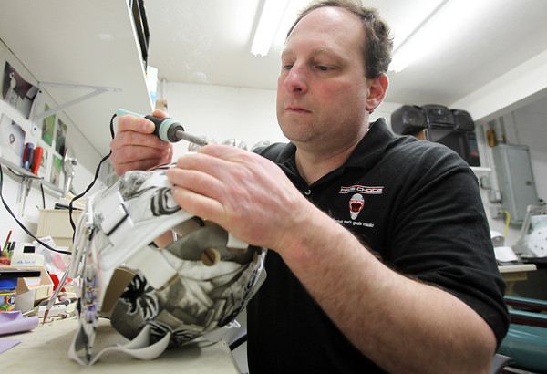 Middleton: Dom Malerba, of Middleton, makes goalie masks for numerous NHL players. Here he puts the finishing touches on attaching the back plate of a completed mask. David Le/Salem News
