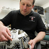 Middleton: Dom Malerba, of Middleton, makes goalie masks for numerous NHL players. Malerba attaches the back plate on a mask and makes some finishing touches. David Le/Salem News