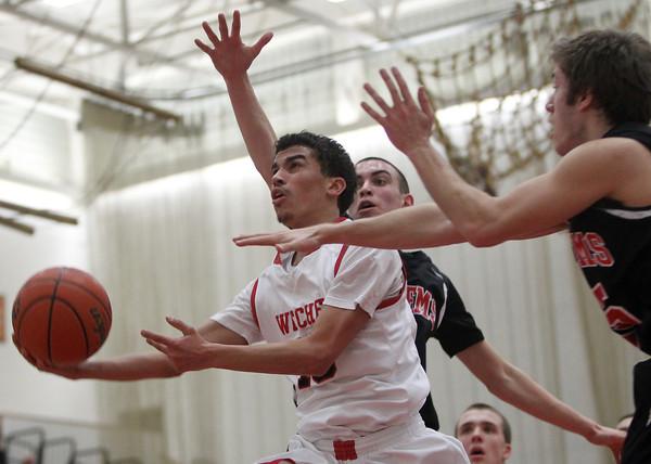 Salem: Salem High School junior Marvin Baez tries to flip home a shot in between two Winchester defenders. David Le/Salem News