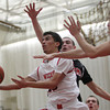 Salem: Salem High School junior Marvin Baez tries to flip home a shot in between two Winchester defenders. David Le/Salem News
