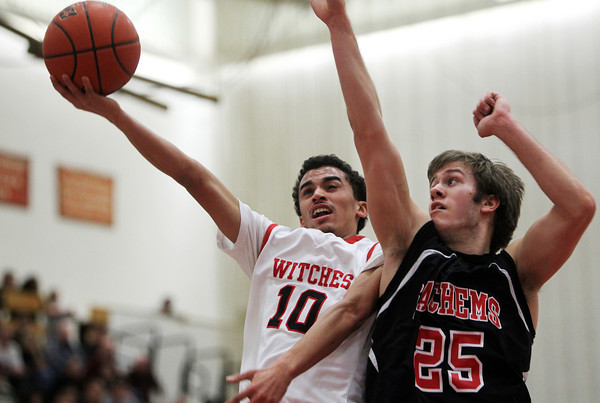 Salem: Salem High School junior Marvin Baez drives hard to the hoop and goes up for a layup while Winchester senior Ryan Murphy rises up for a block attempt on Tuesday evening. David Le/Salem News