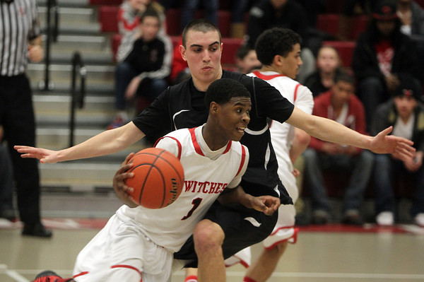Salem: Salem High School senior Christian Dunston blows past Winchester senior Tim Mangano during the first half of play on Tuesday evening. Dunston scored 27 points and led the Witches to a 67-65 win over the Sachems.  David Le/Salem News