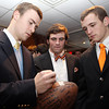 Danvers: Beverly senior captain Brendan Flaherty, left, signs a football with the names of all varsity football players on it as classmates Brian Perry, center, and Dave Rollins, right, look on prior to the start of their annual football banquet at the Danversport Yacht Club. David Le/The Salem News