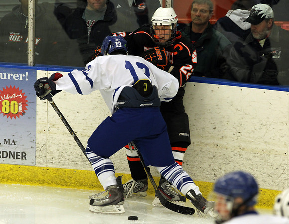 Salem: Beverly junior center Connor Irving, right, tries to fight through a check from Danvers sophomore defenseman Mike Disciullo and battles for a puck against the boards during the third period of play on Saturday afternoon. Beverly (7-0) remained undefeated on the season, handily beating Danvers (5-2-1) 3-0 at Rockett Arena. David Le/Salem News