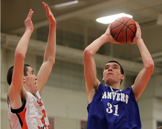 Beverly: Danvers senior forward Dan Connors takes a jump shot while being contested by Beverly junior Nick Cross, left, during the third quarter of play on Tuesday. The Falcons edged out the Panthers 49-47 in a closely contested NEC matchup at Beverly High School. David Le/Salem News