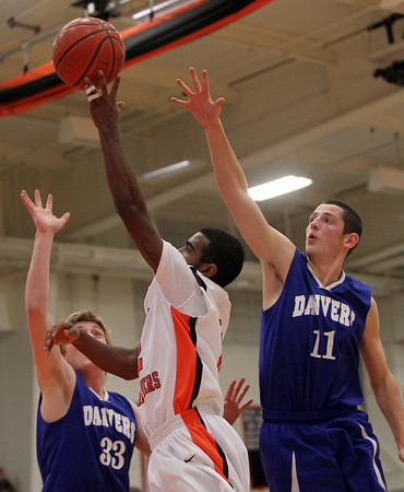 Beverly: Beverly junior guard Jonangel Franco, center, puts up a floating shot around Danvers senior Eric Martin, right, and senior Jake Cawlina, left, in the second quarter of play. David Le/Salem News