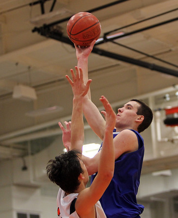 Beverly: Danvers senior forward Dan Connors, right, takes a hook shot over Beverly junior Jonathan Berchoff, left, on Tuesday evening. David Le/Salem News