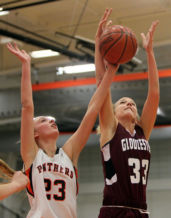 Beverly: Beverly High School junior forward Bridget Keaton, left, battles for a rebound with Gloucester senior Marlee Melvin, right, during the first quarter of play on Friday evening. David Le/The Salem News