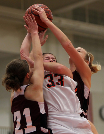 Beverly: Beverly High School junior forward Mary Cate Flaherty has her layup attempt blocked by Gloucester's Katherine Ciaramitaro, left, and Kali Cook, right, during the second quarter of play on Friday evening. David Le/The Salem News