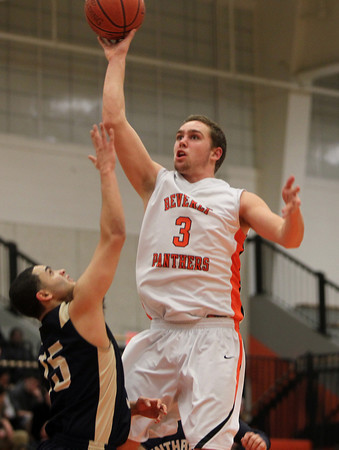 Beverly: Beverly senior forward Cam Rogers, right, releases a floater over Winthrop senior Ervin DeJesus, left, during the second half of play on Friday evening. David Le/Salem News