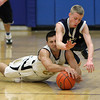 Danvers: Bishop Fenwick senior Joe Buccheri, left, and Peabody senior Maynard Wheeler, right, collide as they dive on the floor to win a loose ball during the second half of play on Monday afternoon. David Le/Salem News