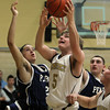 Bishop Fenwick junior Matt Costello, center, goes up strong for a layup ahead of the block attempts from Peabody senior Foni Makoci, left, and junior Brian Onessimo, right, on Monday afternoon. David Le/Salem News