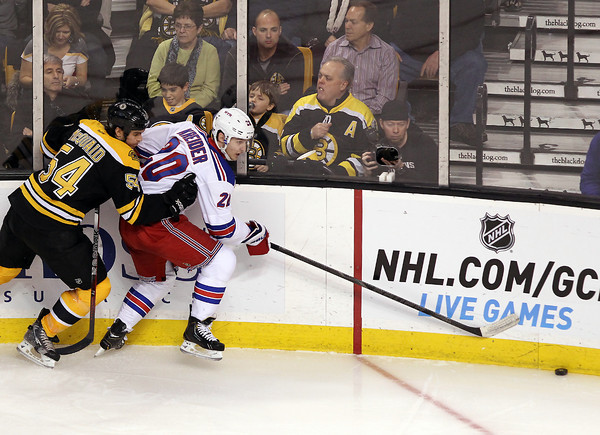 Boston: Boxford native and New York Rangers winger Chris Kreider (20) battles for the puck along the boards with Boston Bruins defenseman Adam McQuaid (54). David Le/Salem News