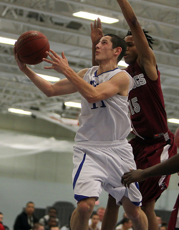 Danvers: Danvers High School senior guard Eric Martin flips in a layup off the glass while being defended by Lynn English forward Johnny HIlaire, right, on Wednesday evening. David Le/Salem News